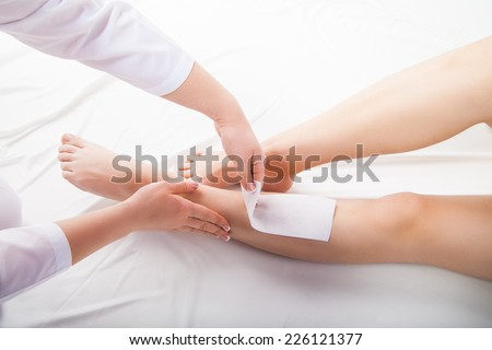 Beautician waxing  woman legs in a spa salon - stock photo