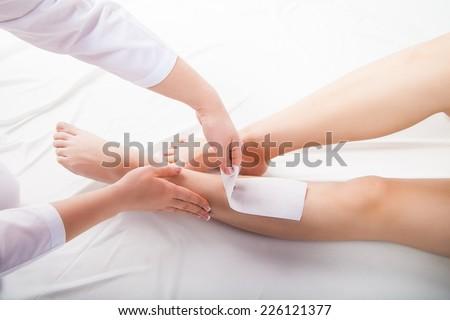 Beautician waxing  woman legs in a spa salon - stock photo