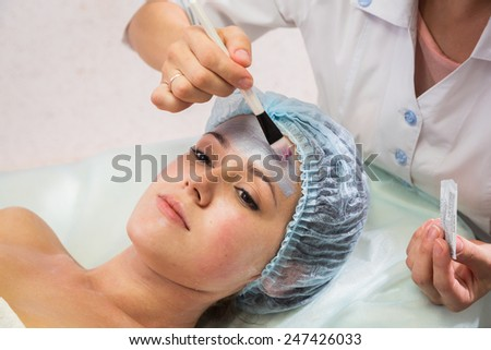 Beautician working on a face model in a spa salon. The process of cosmetic facial treatments. Beautician applying mask on the face of the model. Rejuvenation, skin nutrition. - stock photo