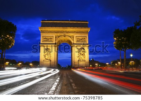 Beautifly lit Triumph Arch at night with light traces of passing cars. Paris, France. - stock photo