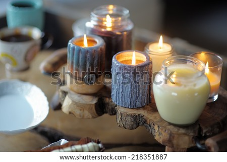 Beautiful ablaze candle on the wooden table - stock photo
