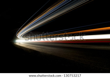 Beautiful abstract lights in a car tunnel in orange, white, blue - stock photo
