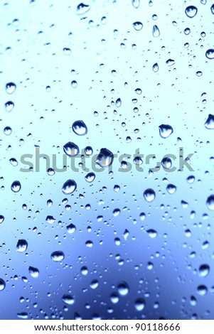 Beautiful abstraction with water drops over blue glass background(shallow dof) - stock photo