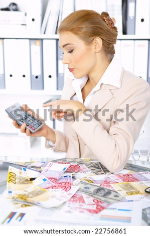 Beautiful accountant using calculator to count cash - stock photo