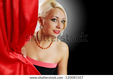 Beautiful actress peeks from behind the curtain - stock photo