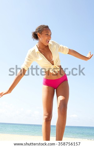 Beautiful adolescent african american healthy teenager carefree on sunny beach destination against a blue summer sky, outdoors. Adolescent joyful expressions and wellness lifestyle, colorful exterior. - stock photo