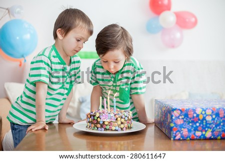 Beautiful adorable four year old boy and his brother in green shirts, celebrating his birthday, blowing candles on homemade baked cake, indoor. Birthday party for kids - stock photo