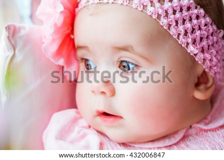 Beautiful adorable little girl in a pink dress with a bow, smiling. A happy childhood of the child. Closeup, macro. - stock photo