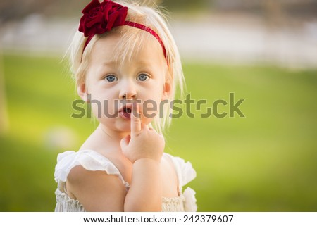 Beautiful Adorable Little Girl With Her Finger on Her Mouth Wearing White Dress In A Grass Field. - stock photo