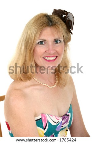 Beautiful adorned middle aged woman sits back ready to go with Flower in Her Hair - stock photo