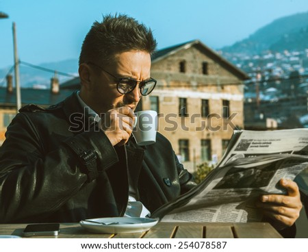 Beautiful adult business man drink coffee and read newspaper outdoors - stock photo