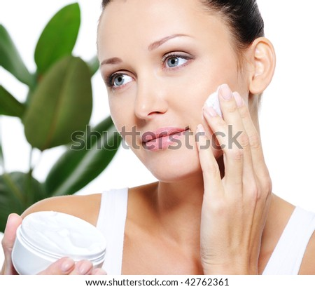 Beautiful adult woman applying moisturizer cream for her pretty face - stock photo