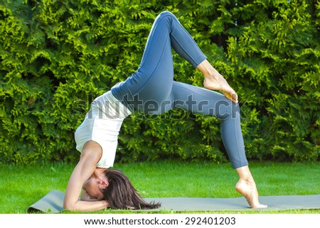 beautiful adult woman doing yoga on a green grass at summer morning in park - stock photo