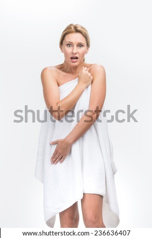 Beautiful adult woman with fresh healthy skin covering herself. Portrait of scared naked woman in towel - stock photo