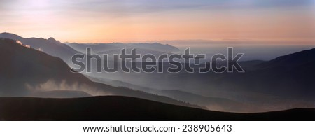 Beautiful aerial perspective in the mountains, haze in the first rays of the sun - stock photo