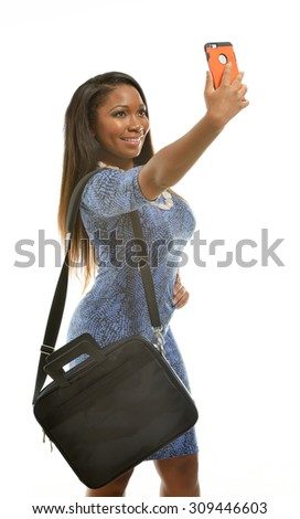 Beautiful African-American business  woman in blue dress and carrying a brief case takes a selfie (photo) with her smartphone - stock photo