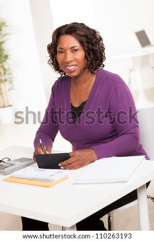 Beautiful African American female executive with dark brown hair at work in an office setting wearing a purple sweater. - stock photo