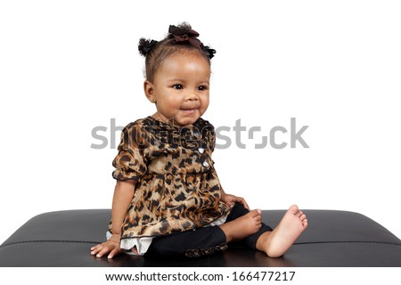 Beautiful African American Infant sitting upright dressed up in a leopard print frilly dressed on a leather stool isolated on a white background.  - stock photo