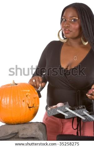 Beautiful African-American make up artist applying makeup on Halloween carved pumpkin (Jack O' Lantern) - stock photo