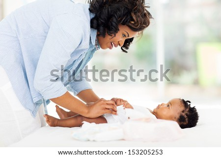 beautiful african american mother changing baby's diaper - stock photo