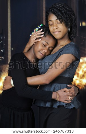 Beautiful African American sisters lovingly embracing each other before nighttime windows and white Christmas lights. - stock photo