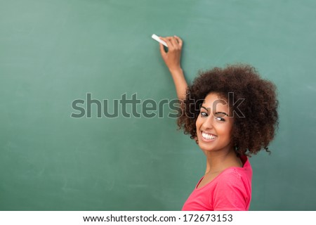 Beautiful African American student or teacher standing in front of the blank class blackboard with a piece of chalk in her hand ready to commence writing - stock photo