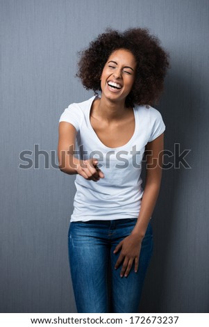 Beautiful African American teenager with frizzy afro hair laughing and pointing at the camera against a grey background - stock photo