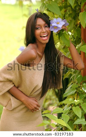 beautiful African American woman enjoying spring flowers in the garden - stock photo