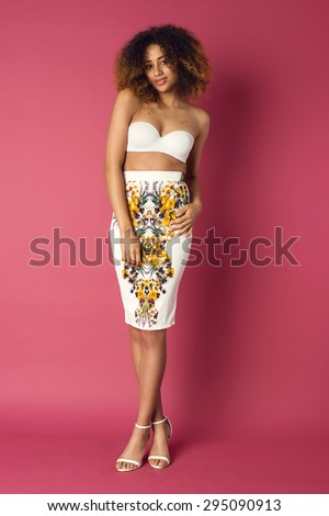 Beautiful African American woman posing in nice flower pattern skirt and white bra on a pink background. Fashion photo with afro hairstyle. - stock photo