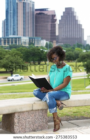 Beautiful African American woman reading a  book, Austin, Texas cityscape on background - stock photo