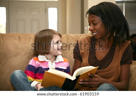 Beautiful african american woman reading to a 5 year old girl at home. - stock photo