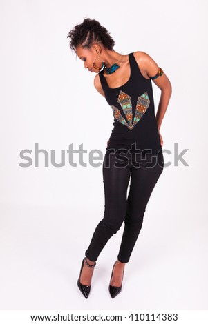 Beautiful African American woman with curly hairs looking to her high heels - stock photo
