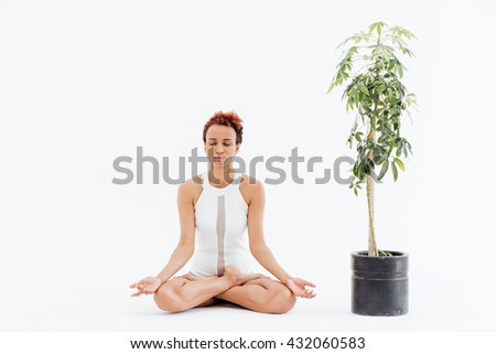Beautiful african american young woman meditating in lotus pose near the tree in pot over white background - stock photo