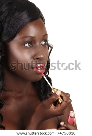 beautiful African American young woman with long curly hair applying red lip gloss to her full lips - easy to extend background for copy space over white. - stock photo