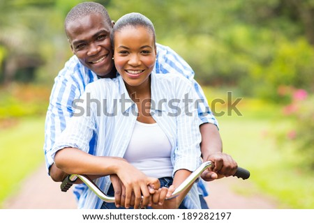 beautiful african couple riding bicycle together outdoors - stock photo