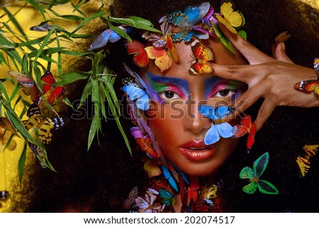 beautiful african girl surrounded by butterflies - stock photo