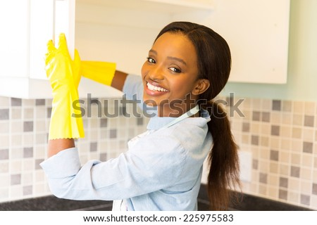 beautiful african woman cleaning cupboard - stock photo