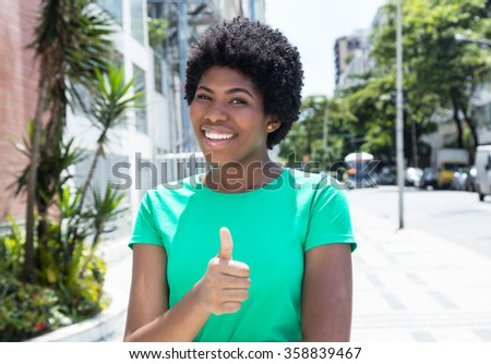 Beautiful african woman in a green shirt in the city - stock photo