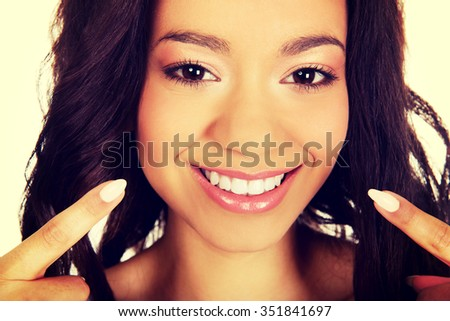Beautiful african woman pointing to teeth. - stock photo