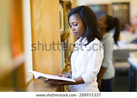 beautiful afro american college girl reading a book in library - stock photo