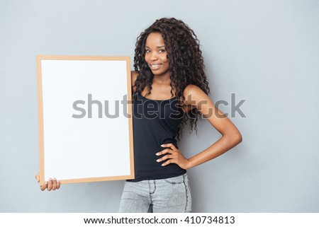 Beautiful afro american woman showing blank board over gray background - stock photo