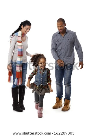 Beautiful afro little girl running, parents watching from behind. - stock photo