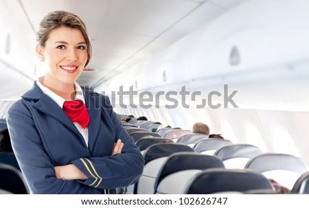 Beautiful air hostess in an airplane smiling - stock photo