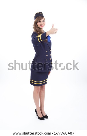 Beautiful air hostess showing thumb up gesture isolated on white background - stock photo