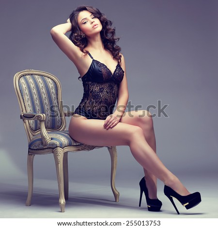 Beautiful alluring young woman in sexy black lingerie sitting in antique armchair  - stock photo