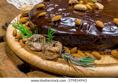 Beautiful almond cake with rosemary and dried figs sitting on old wooden table covered with lace - stock photo