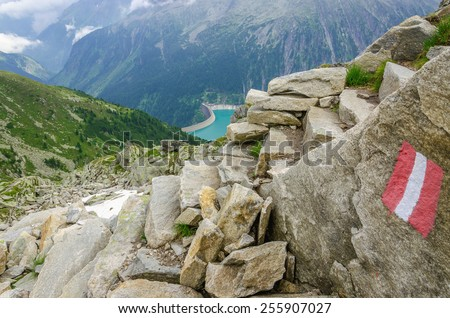 Beautiful alpine landscape with trail blazing and azure mountain lake in the background, Zillertal Alps, Austria - stock photo