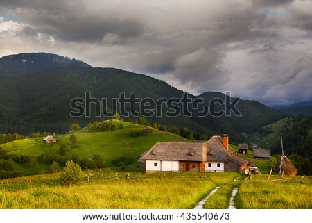 Beautiful alpine meadow with green grass. landscape on wild transylvania hills. Holbav. Romania. Low key, dark background, spot lighting, and rich Old Masters - stock photo