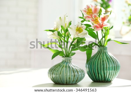 Beautiful Alstroemeria flowers in aquamarine vases on window background - stock photo