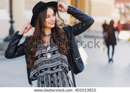 Beautiful amazing brunette woman with long wavy hairstyle in spring or fall stylish  urban outfit walking  on the street. Red lips, slim body. Street fashion concept.  - stock photo